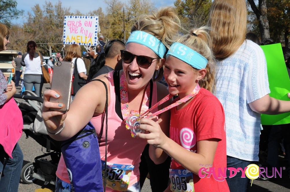 Great Candy Run Minneapolis: Woman and Child admire race medals as they take a selfie.